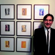 Jay Asquini in front of some of his works.